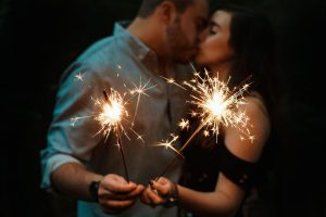 "A couple kisses while holding sparklers representing how marriage counseling and couples therapy can bring the ""spark"" back into your relationship!"