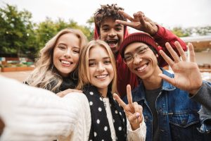 A group of friends stand smiling for picture with peace signs and waving. They are feeling much better after starting online therapy for college students in Virginia with Monday Courage. You can get online counseling for college students in virginia here too! We serve Roanoke, Arlington, Lynchburg, Fredericksburg and more.