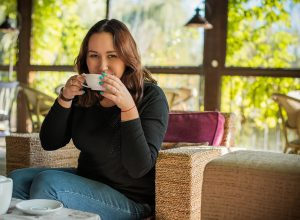 A woman smiles while drinking a cup of coffee. She is feeling much happier after starting online therapy in Virginia with Monday Courage. You can get help with trauma therapy, counseling for college students and more with online therapy in VA.