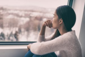 A girl looks out the window, looking upset. She is waiting to start trauma therapy in Lynchburg, VA with Monday Courage Counseling in Virginia.