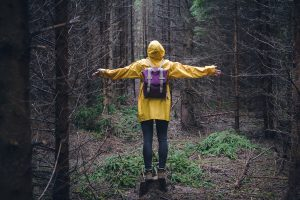 A woman stands in the forest with her arms spread out. She is feeling better after starting trauma therapy in Lynchburg, VA with Monday Courage Counseling for Trauma Therapy in Virginia.