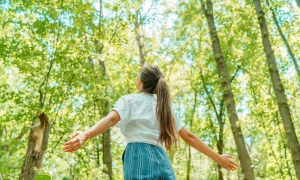 A girl walks through the forest. She is feeling happy after starting grief counseling in Lynchburg, VA with Monday Courage.
