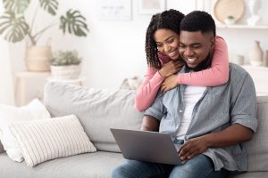 A couple sits next to each other on a couch smiling. They are feeling happy since starting online premarital counseling in VA with Monday Courage.