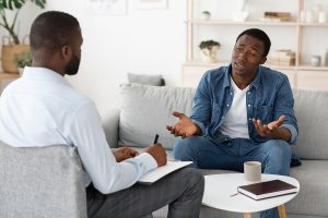 A man sits in a counseling session. He has begun counseling for divorce recovery in Lynchburg, VA with Monday Courage.