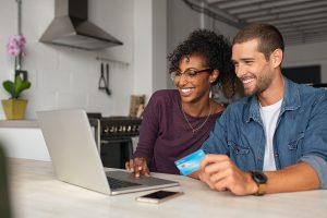 A couple smile together while using a laptop to pay for online marriage counseling in Virginia with Monday Courage.